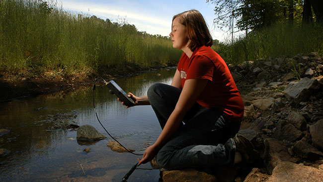 Photo of woman analyzing water quality in a stream