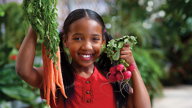 Photo of girl holding up organic produce